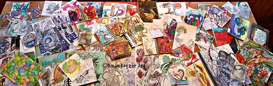 Dawn-Kotzer-Doodle-ART. Dawn Kotzer© Doodle ART alt text: 6 foot wooden table covered with dozens of original doodles and small art pieces done by Dawn Kotzer.
